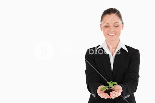 Pretty woman in suit holding a small plant