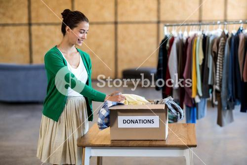 Young woman sorting clothes from donation box