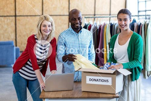 Colleagues sorting clothes from donation box