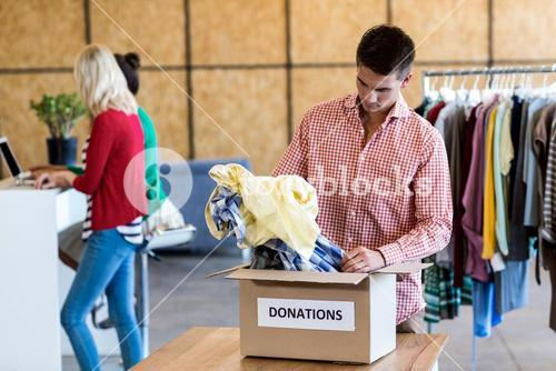 Young man sorting clothes from donation box