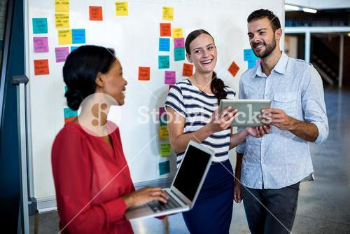Colleagues standing by white board