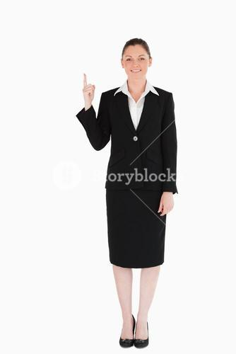 Good looking female in suit pointing at a copy space