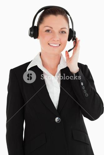 Portrait of a good looking woman in suit using headphones and posing