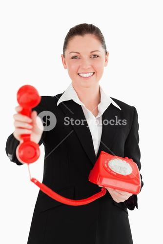 Good looking woman in suit holding a red telephone