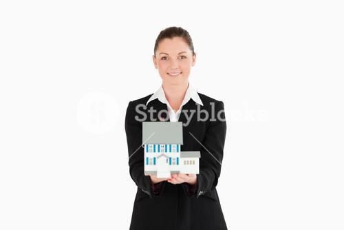 Pretty woman in suit holding a miniature house