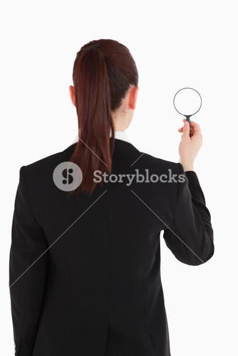 Beautiful woman in suit being back to the camera and holding a magnifyng glass while standing