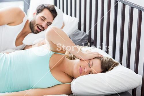 Woman ignoring while man snoring on bed