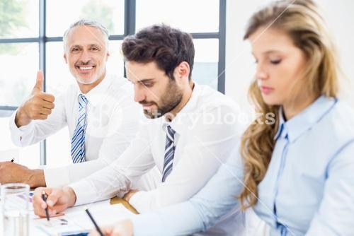 Businessman showing thumbs up in a meeting