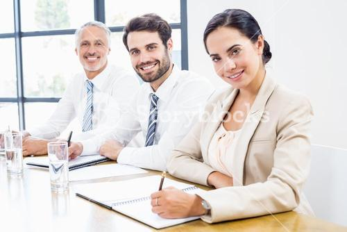 Business colleagues writing in diary