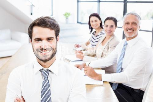 One businessman is standing and three workers are sitting and smiling