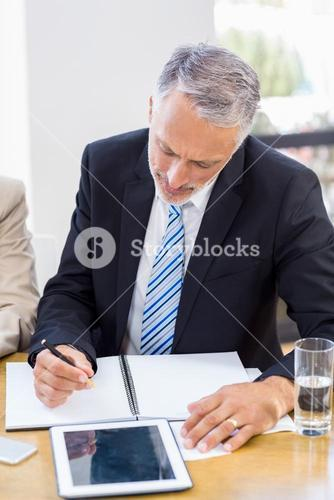 A businessman is taking some notes