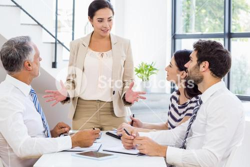 Businesswoman is talking to her colleagues who are listening carefully