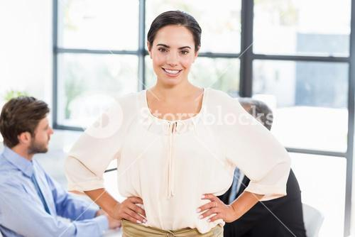 Pretty businesswoman smiling with hands on hips