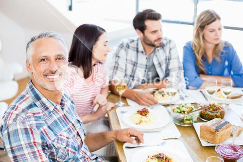 Man sitting with friends at dinning table