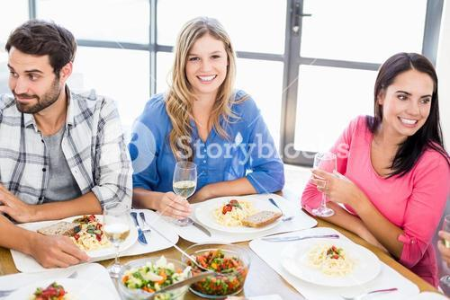 Woman sitting with friends at dinning table