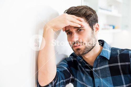Depressed man leaning on wall