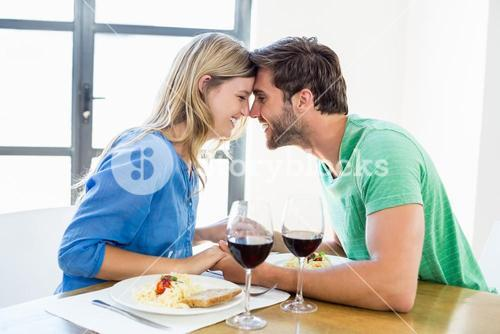 Young couple sitting face to face at dinning table