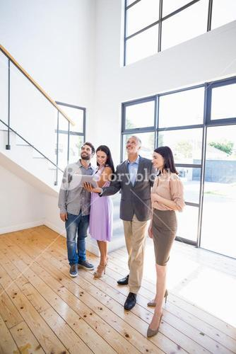 Real estate showing a house project on a digital tablet to young couple