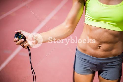 Mid-section of woman holding stop watch