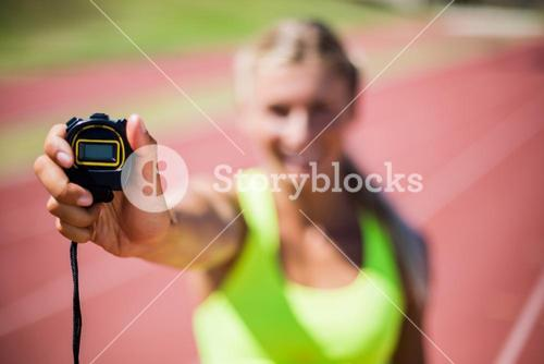 Female athlete showing stop watch