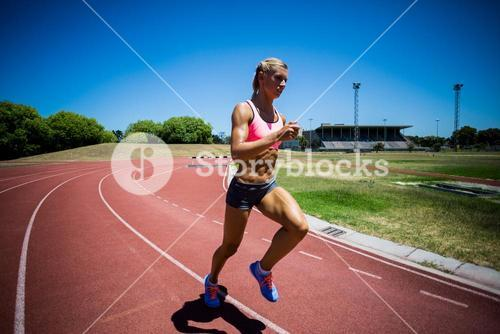Female athlete running on the racing track