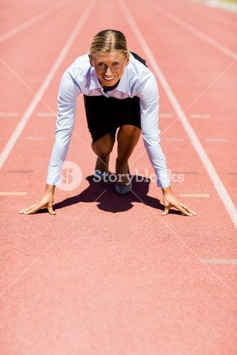 Businesswoman ready to run on running track