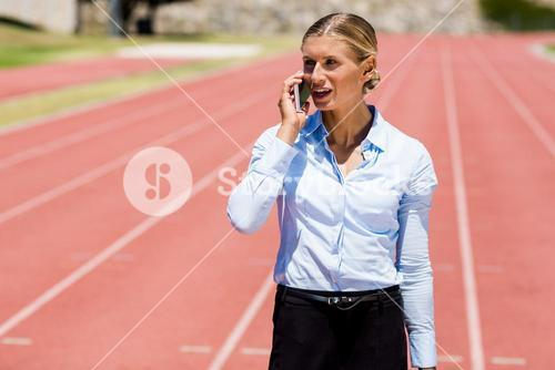 Businesswoman talking on phone on a running track