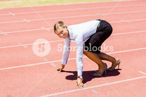 Portrait of businesswoman ready to run on running track