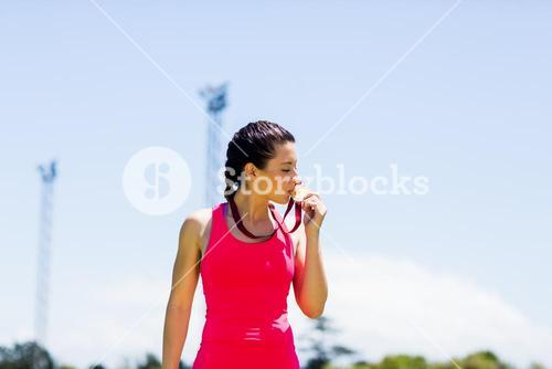 Female athlete kissing her gold medals