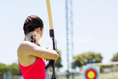Female athlete practicing archery