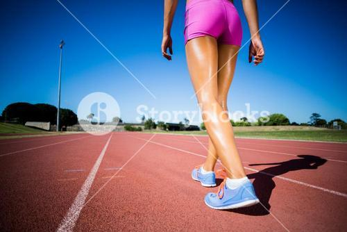 Female athlete walking on the racing track
