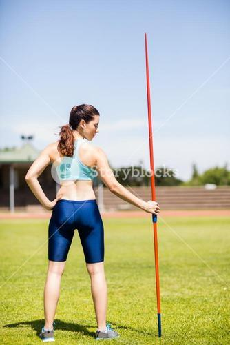 Rear view of female athlete holding a javelin in stadium