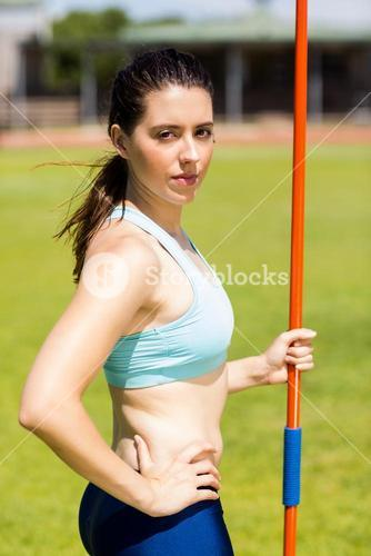Portrait of female athlete standing with javelin
