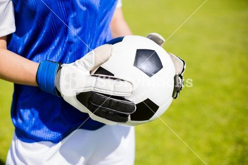 Mid-section of soccer player standing with a ball