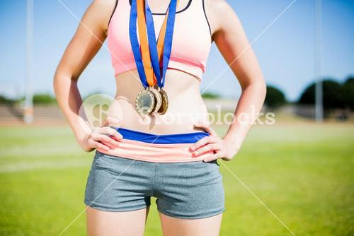 Mid section of female athlete with gold medals around her neck