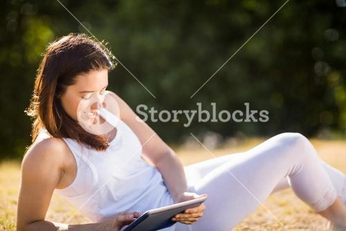 Woman sitting on grass and using digital tablet