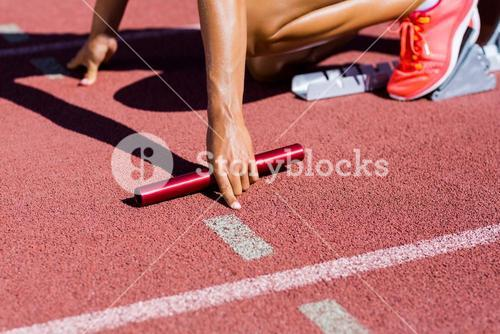 Female athlete ready to start the relay race