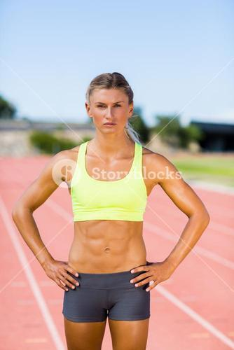 Confident female athlete standing with hand on hip