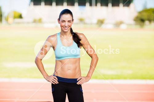 Portrait of female athlete standing with hands on hips