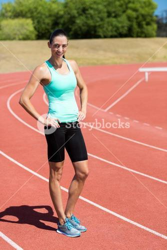 Portrait of female athlete standing with hands on hi