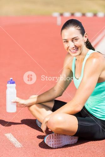 Portrait of tired female athlete sitting with water bottle