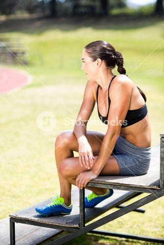 Female athlete sitting on stand