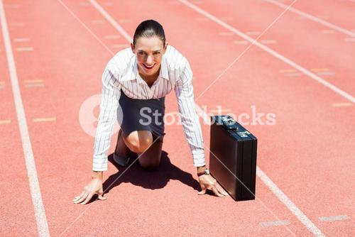 Portrait of happy businesswoman with briefcase in ready to run position