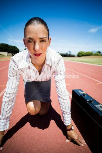 Portrait of confident businesswoman with briefcase in ready to run position