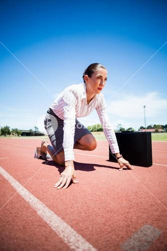 Businesswoman with briefcase in ready to run position