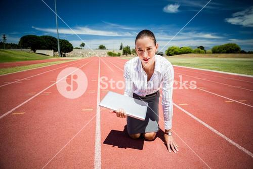 Businesswoman ready to run with a laptop