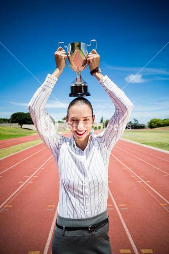 Portrait of happy businesswoman holding a trophy over her head