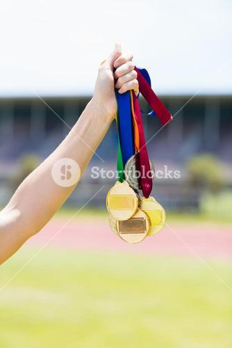 Female athlete holding her gold medals