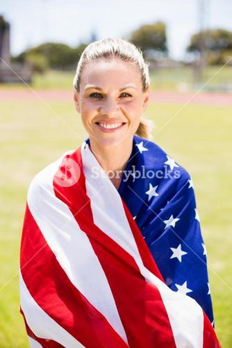 Portrait of female athlete wrapped in american flag