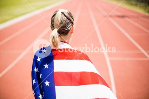 Rear view of female athlete wrapped in american flag